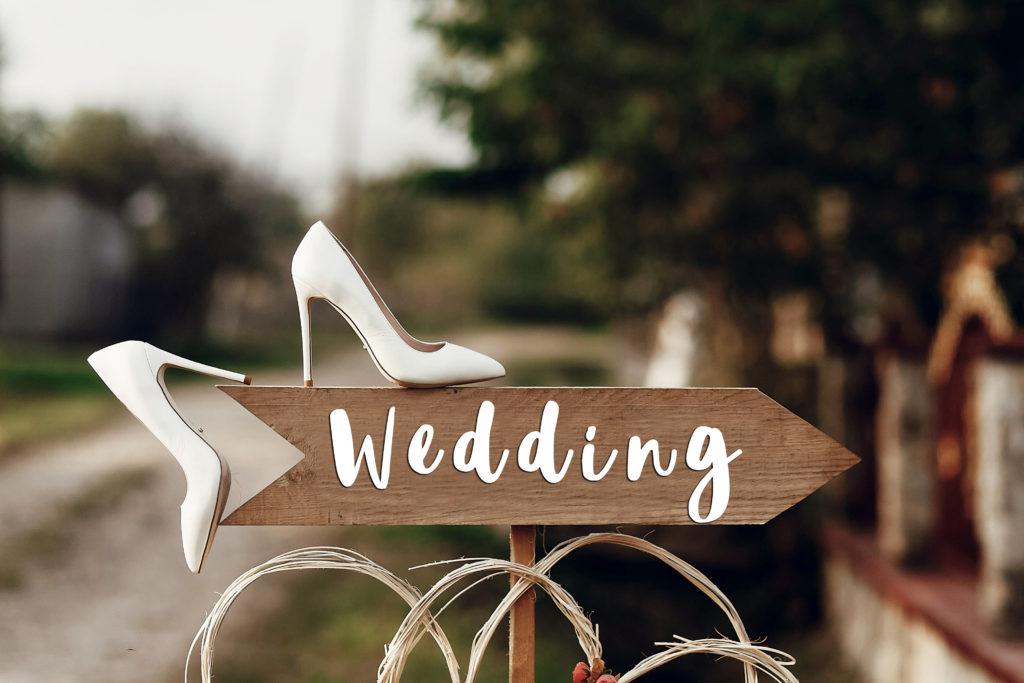 Pancarte indiquant Wedding et les chaussures blanches de la mariée