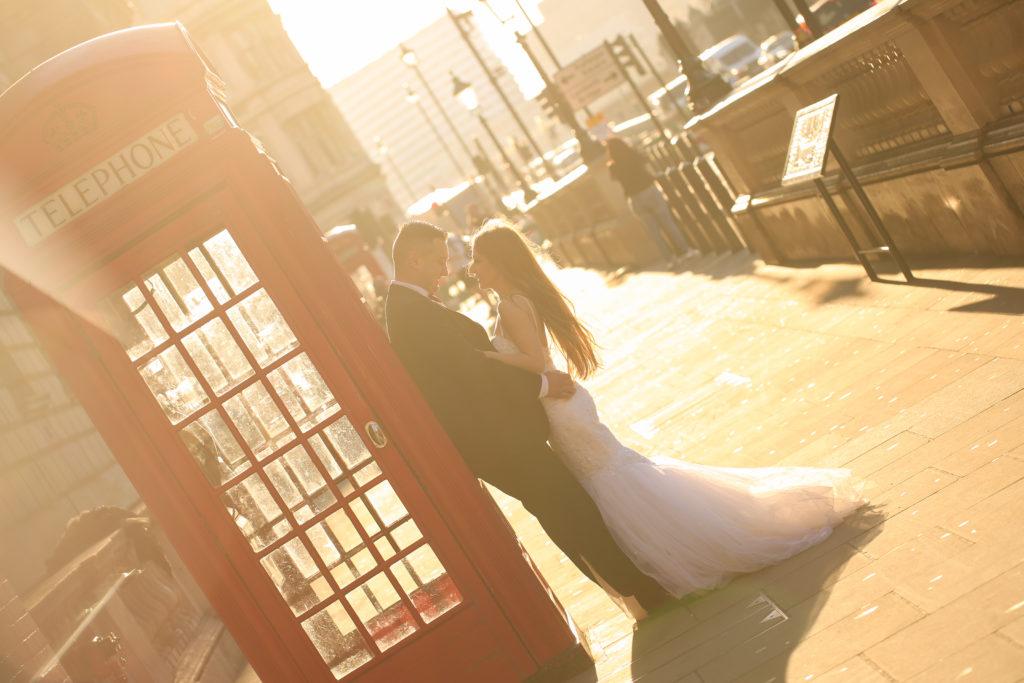 Jeunes mariés à côté d'une cabine téléphonique à Londres