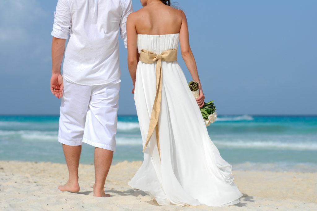 Jeune couple marié par élopement marchant sur une belle plage