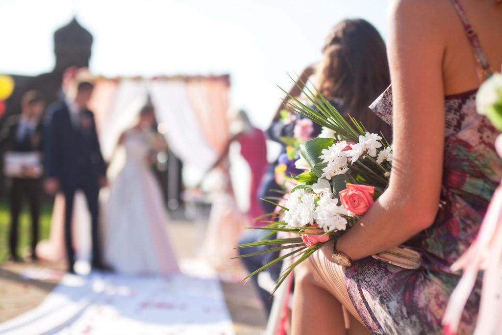 Cérémonie de mariage en extérieur avec vue sur le bouquet, l'allée centrale et les mariés