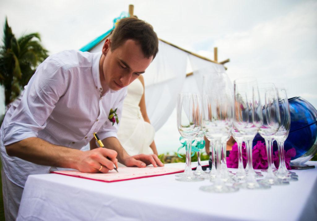 Le marié signe le registre d'union pendant la cérémonie laïque de mariage